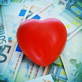 a red heart on a pile euro banknotes depicting the idea of love for the money or the cost of love or