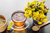 Healthy Tea In Glass Cup Closeup, Bucket With Coltsfoot Flowers And Mortar