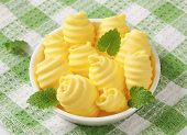 bowl of yellowish butter curls, on the table with green square linen