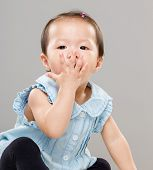 Little girl with hand cover her mouth