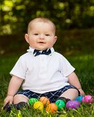 image of laying eggs  - Cute infant baby boy playing with Easter eggs - JPG