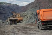 foto of iron ore  - Heavy mining trucks being loaded with iron ore on the opencast - JPG