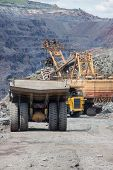 picture of iron ore  - Heavy mining trucks being loaded with iron ore on the opencast - JPG