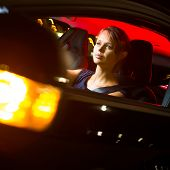Driving a car at night - pretty, young woman driving her modern car at night, in a city (shallow DOF