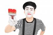 Mime artist holding a paintbrush isolated against white background