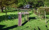 stock photo of seesaw  - Children playground on green grass with staircase and seesaw - JPG