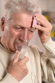 Elderly man making inhalation