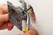 image of electrician  - Electrician hands installing wires into electrical outlet  - JPG