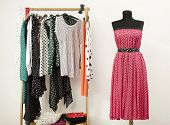 stock photo of mannequin  - Dressing closet with polka dots clothes arranged on hangers and a pink dress on a mannequin - JPG