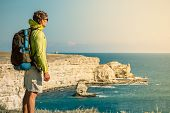 stock photo of survival  - Man Traveler with backpack relaxing outdoor Sea and Rocks coastal on background Freedom Lifestyle concept - JPG