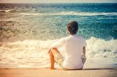 Man Traveler sitting on beach seaside looking on sea waves summer vacations Lifestyle concept