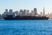 San Francisco Skyline with merchant ship cruising bay at California USA