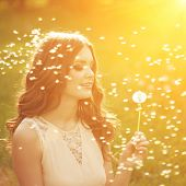 Beautiful young woman blowing a dandelion. Trendy young girl at sunset with flower
