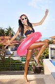 stock photo of flesh air  - Young woman in white sunglasses with pink inner tube walking at tropical resort in summer day - JPG