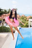 picture of flesh air  - Young woman in white sunglasses with pink inner tube having fun near pool at tropical resort in summer day - JPG