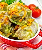 Cabbage stuffed and carrots in red pan on board