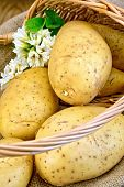 Potatoes yellow in basket with flower on board