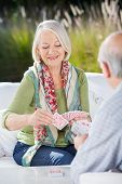 Happy senior woman playing cards with man at nursing home porch