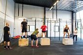 Group of young male and female athletes box jumping