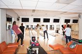 Rear view of young friends bowling in club