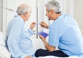 Male caretaker guiding prescription to senior man in bedroom at nursing home