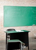 View of empty classroom with greenboard and furniture