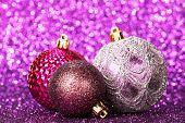 Beautiful purple christmas balls on abstract glitter background close-up