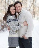 Happy Couple With Mistletoe Having Fun In The Winter Park