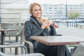 Smiling Pretty Blond Woman in Black Fashion Having Coffee Break at the Cafe Alone.