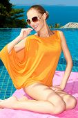 Smiling Pretty Woman Sitting on Pink Cloth at Poolside in Orange Summer Fashion Outfit.