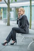 Smiling Young Businesswoman in Black Corporate Attire Talking to Someone Through Phone at Outdoor Bench.