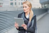 Attractive stylish young woman standing outdoors in an urban walkway holding a tablet and staring thoughtfully in front of her