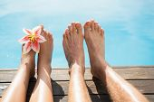 Close up of couple's bare feet against swimming pool on a sunny day
