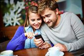Portrait of young couple with cellular phone searching for information