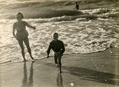 Vintage photo of mother and little son on beach, forties