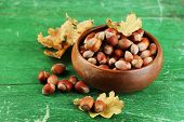 Hazelnuts in wooden bowl on wooden background