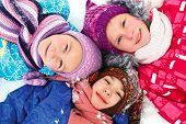 Children Lie On The Snow In Winter And Look Upwards