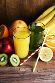 Banana and kiwi juice in glasses and fresh fruits on wooden table on wooden wall background
