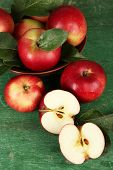 Ripe apples in bowl on wooden background