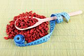 Goji berries in wooden spoon and blue measuring tape line on bamboo mat background