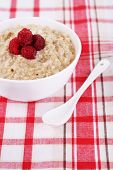 Tasty oatmeal with berries on napkin close-up