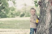 Cute Beautiful Child Having Fun In Warm Autumn Day In Park Outdoors