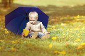 Little Child With Umbrella In Autumn Park
