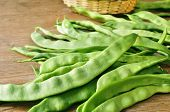 a pile of green bean pods on a wooden table
