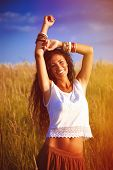 smiling beautiful woman with long curly hair in boho style  stand in grass field