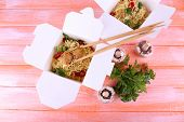Chinese noodles with meat and pepper in takeaway boxes on pink background