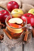 Apple cider with cinnamon sticks, spices and fresh apples on wooden background