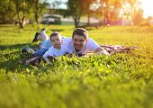 Happy Father And Son Having Fun Lying On The Grass In Summer Sunny Day