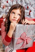 image of sad christmas  - Portrait Of A Sad Little Girl With a wrapped Christmas present - JPG