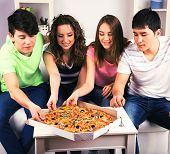 Group of young friends eating pizza in living-room on sofa